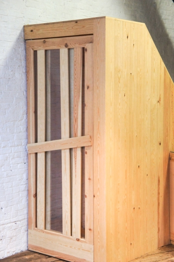 Atelier Antipode See-through pivoting door in pine wood. The wooden laths are set up in an alternating zig zag pattern.