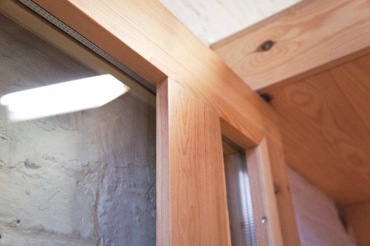 Atelier Antipode   See-through pivoting door in pine wood. The wooden laths are set up in an alternating zig zag pattern. Insulation glass.